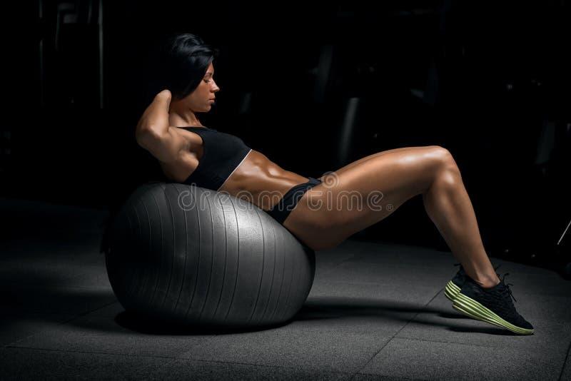 摆在健身房的年轻美丽的健身女孩 免版税库存图片