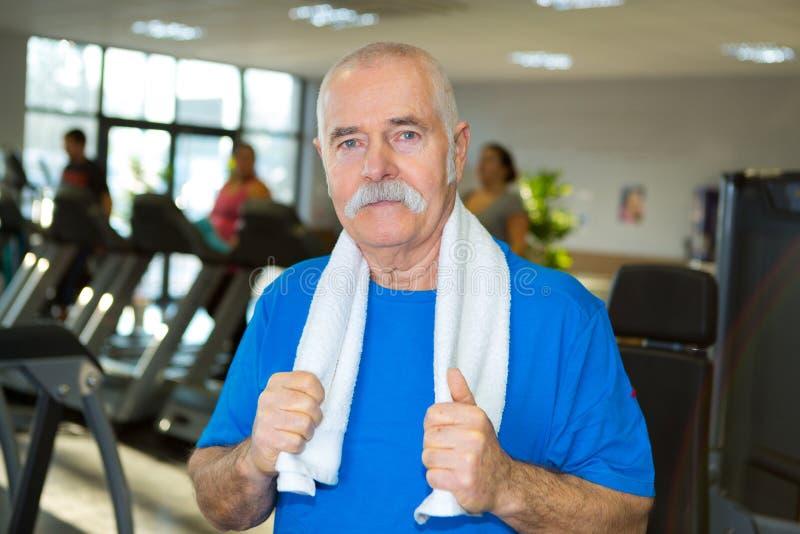 摆在健身房的年长人 免版税库存照片