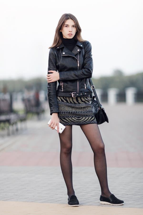 摆在全长户外城市公园的一名年轻俏丽的深色的妇女的情感画象穿巧妙黑皮革的外套对负 免版税图库摄影