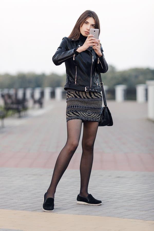 摆在全长户外城市公园的一名年轻俏丽的深色的妇女的情感画象穿黑皮革外套使用smartph 免版税库存照片
