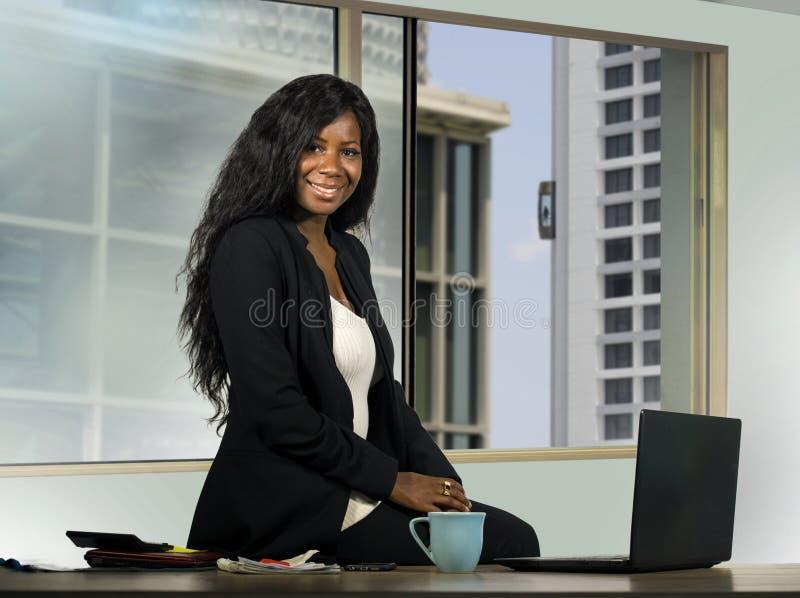 摆在公司工作的年轻美丽和愉快的非裔美国人的女实业家在现代办公计算机书桌在前面 图库摄影
