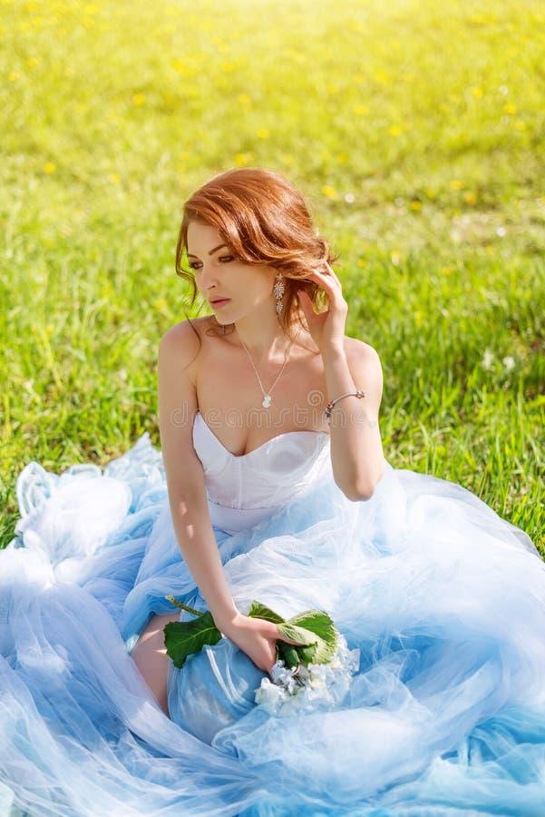 摆在公园或庭院的美丽的年轻新娘画象蓝色礼服的户外在明亮的晴天绿草 库存照片