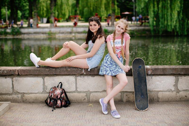 摆在公园的两个都市青少年的女孩 免版税库存照片