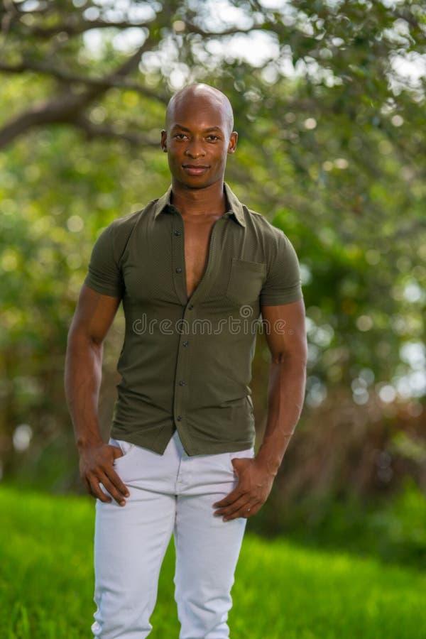 摆在公园的英俊的男性模型 非裔美国人的人画象便衣和拇指的在口袋 免版税库存图片