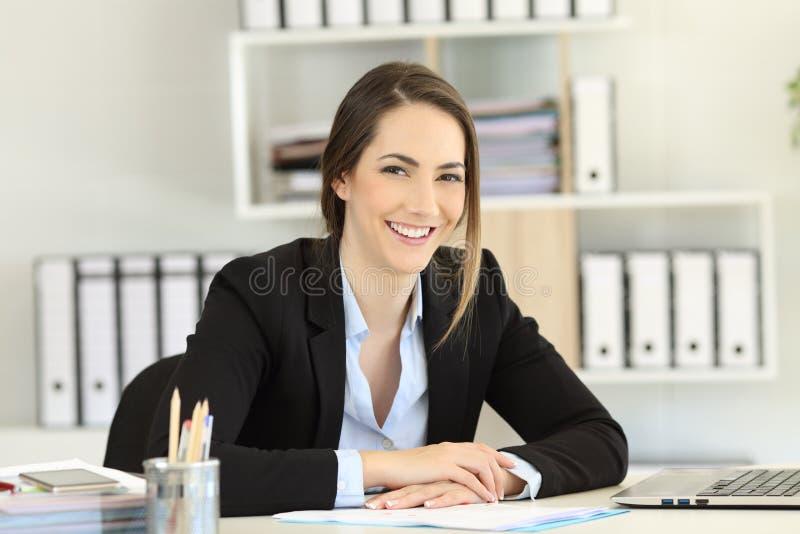 摆在兴高采烈的办公室工作者看照相机 免版税库存照片