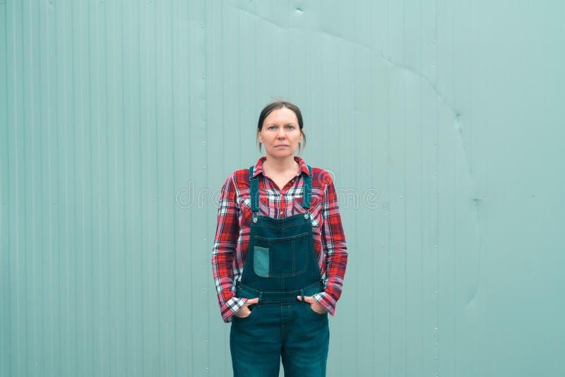 摆在农场的严肃的女性农夫 免版税库存图片