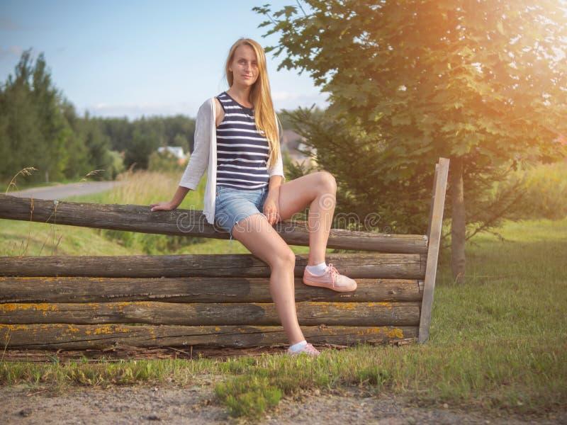 摆在农村风景的年轻时兴的愉快的白肤金发的妇女 免版税库存照片