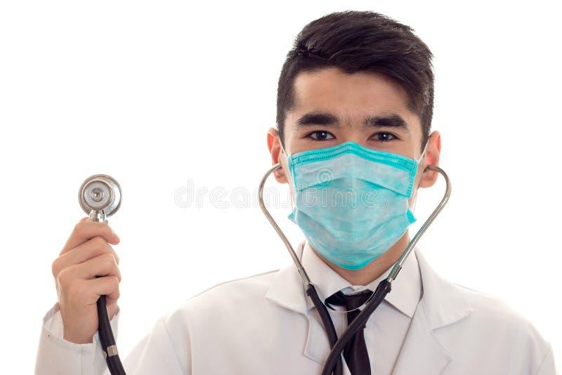 摆在制服和面具的年轻英俊的人医生与在白色背景隔绝的听诊器在演播室 图库摄影