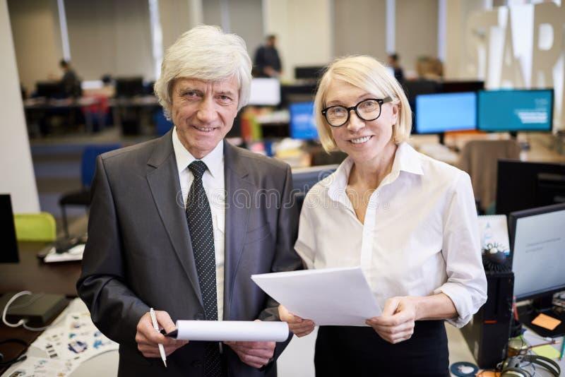 摆在办公室的两个成熟董事 免版税库存图片