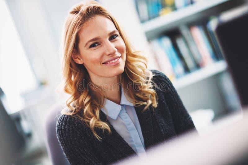 摆在办公室的美好的白肤金发的妇女程序员画象  库存图片