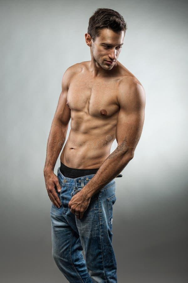 摆在半赤裸的英俊的肌肉人 免版税库存图片
