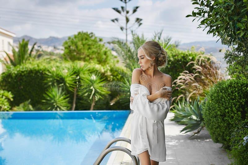 摆在半赤裸近的游泳池的peignoir的美丽,性感,时兴的白肤金发的女孩 库存照片