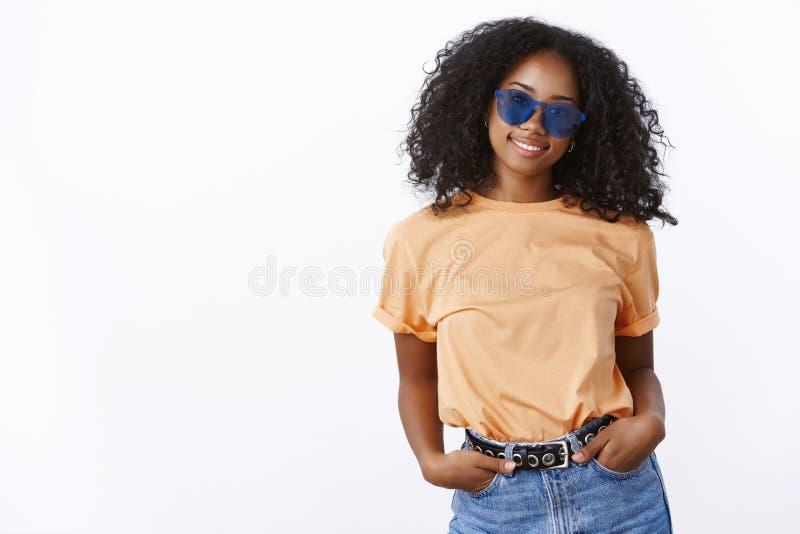 摆在厚颜无耻的喜欢卖弄之人时髦太阳镜的时髦的厚脸皮的悦目现代都市深色皮肤的女孩走享用温暖 免版税库存照片
