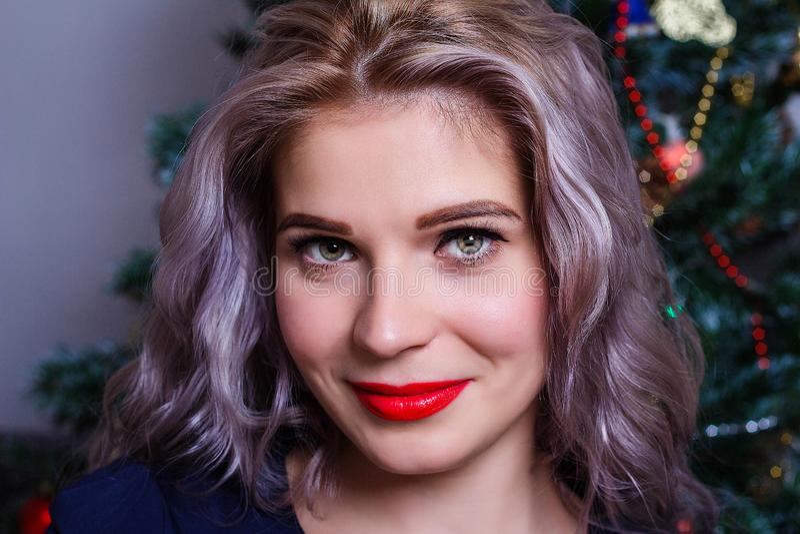 摆在反对圣诞树的背景的一名美丽的白种人妇女的画象 免版税库存照片