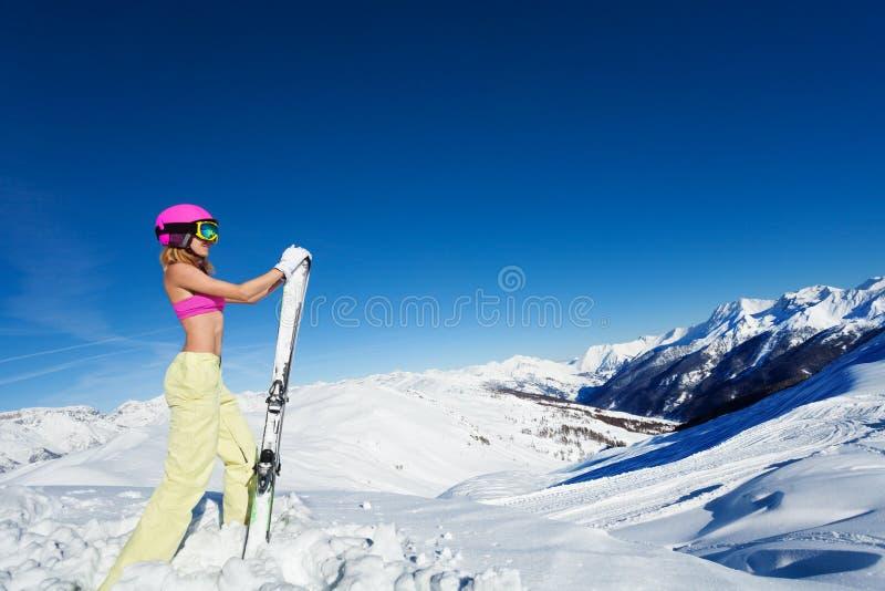 摆在反对多雪的山峰的露胸部的活跃女孩 免版税图库摄影
