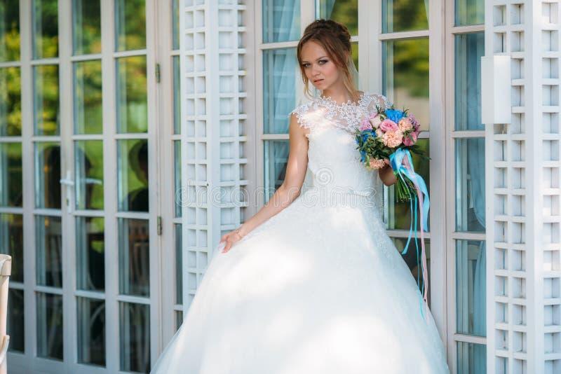 摆在反对污迹玻璃窗的一件闭合的礼服的新娘 女孩举行一件礼服单手和第二 免版税图库摄影