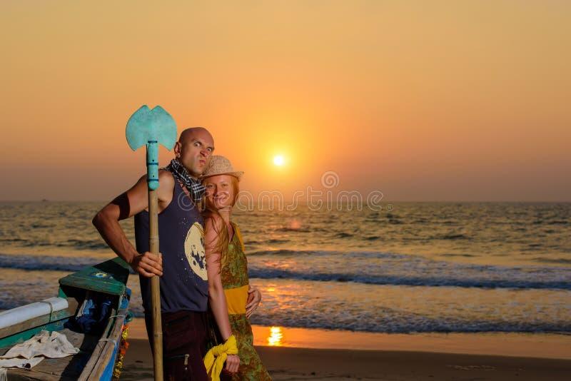 摆在反对海的年轻夫妇在日落 人和女孩唬弄和鬼脸在老木小船附近在海洋海岸 库存照片