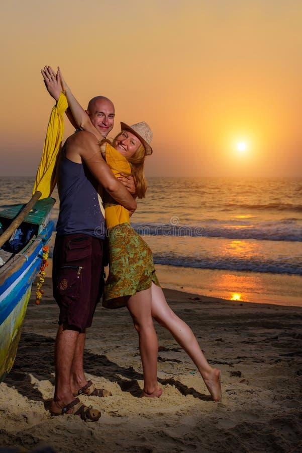 摆在反对海的年轻夫妇在日落 人和女孩唬弄和鬼脸在老木小船附近在海洋海岸 免版税库存照片