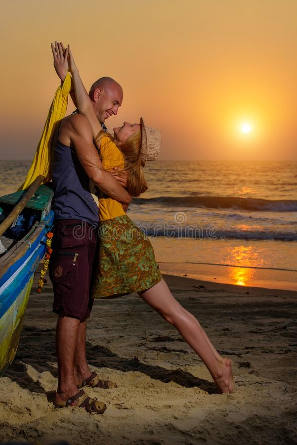 摆在反对海的年轻夫妇在日落 人和女孩唬弄和鬼脸在老木小船附近在海洋海岸 库存图片