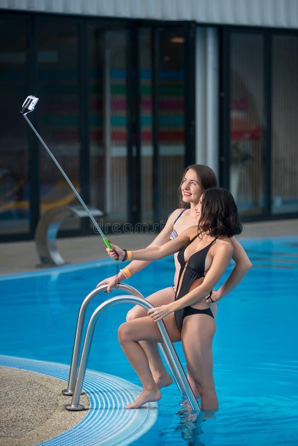 摆在反对游泳池用水和做与monopod的比基尼泳装的两位可爱的女性selfie照片 免版税库存图片