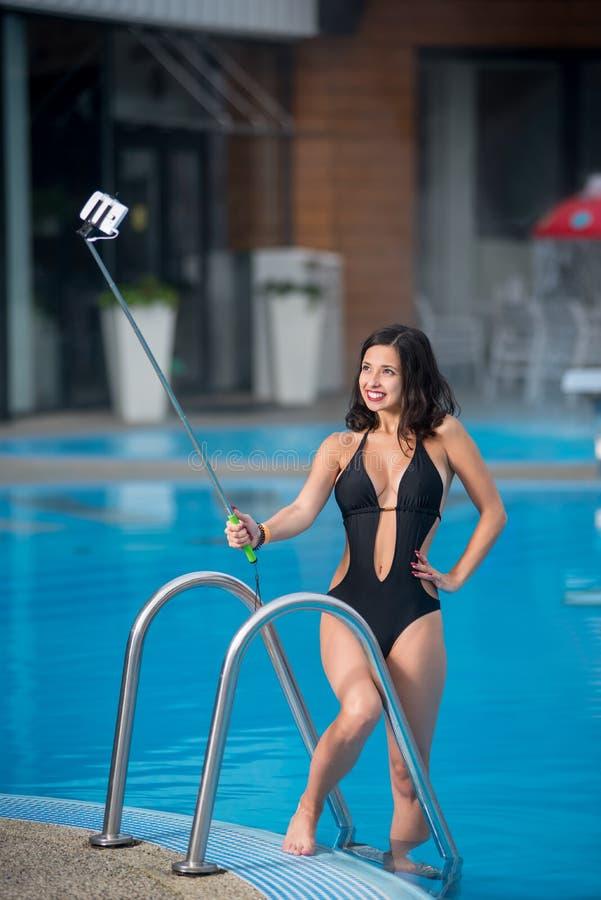 摆在反对游泳池的黑性感的泳装的微笑的女孩在豪华旅游胜地做与monopod的selfie照片 免版税库存照片