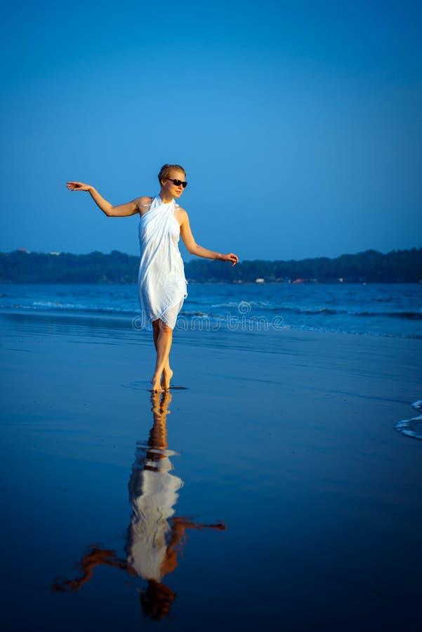 摆在反对白色礼服和太阳镜的蓝色海的年轻愉快的美丽和迷人的金发碧眼的女人 有短发的时髦的女孩 免版税库存图片