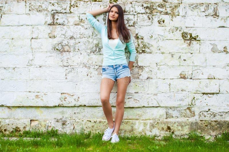 摆在反对石墙背景的短的蓝色牛仔裤短裤的年轻女人 库存照片