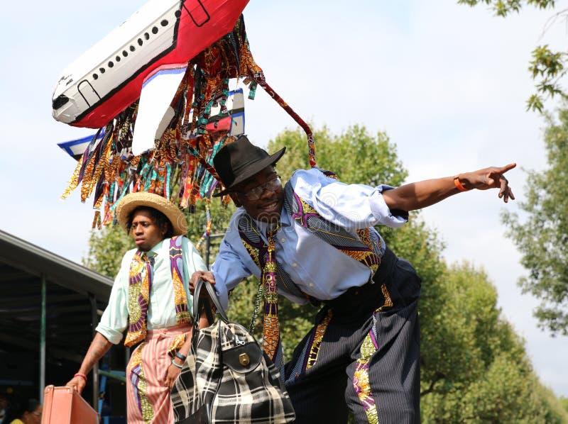 摆在反对蓝天的高跷的诺丁山狂欢节年轻艺术家 免版税库存图片