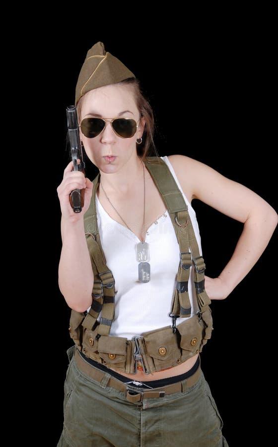 摆在反对黑背景的军服的性感的妇女 库存照片