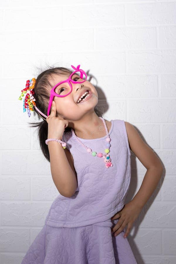 摆在古怪的想法的姿势的女性亚裔儿童女孩,当佩带象冠,项链的一些辅助部件和穿紫色礼服时 库存照片