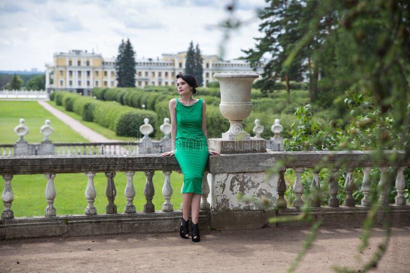 摆在古老宫殿阳台的美丽的深色的女孩  图库摄影