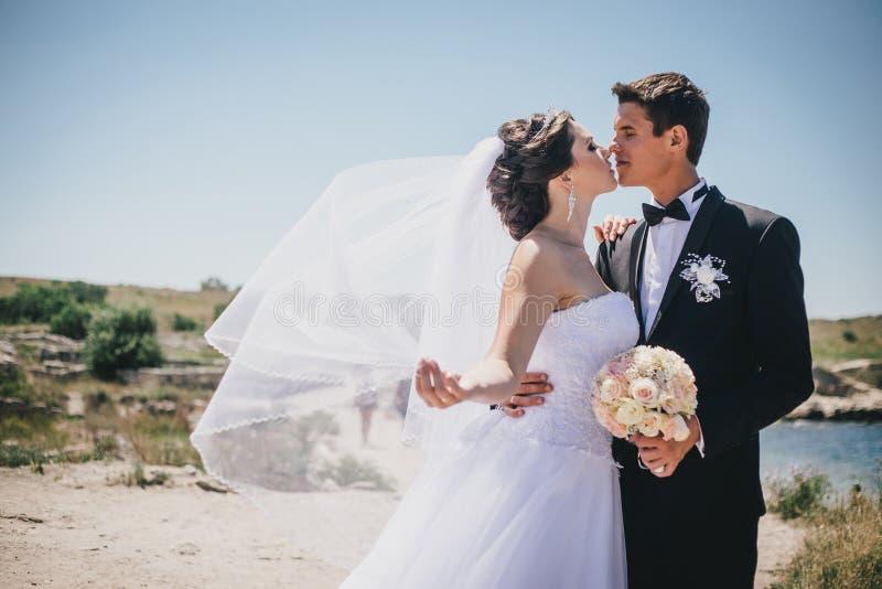 摆在古老废墟背景的新娘和新郎  免版税库存照片