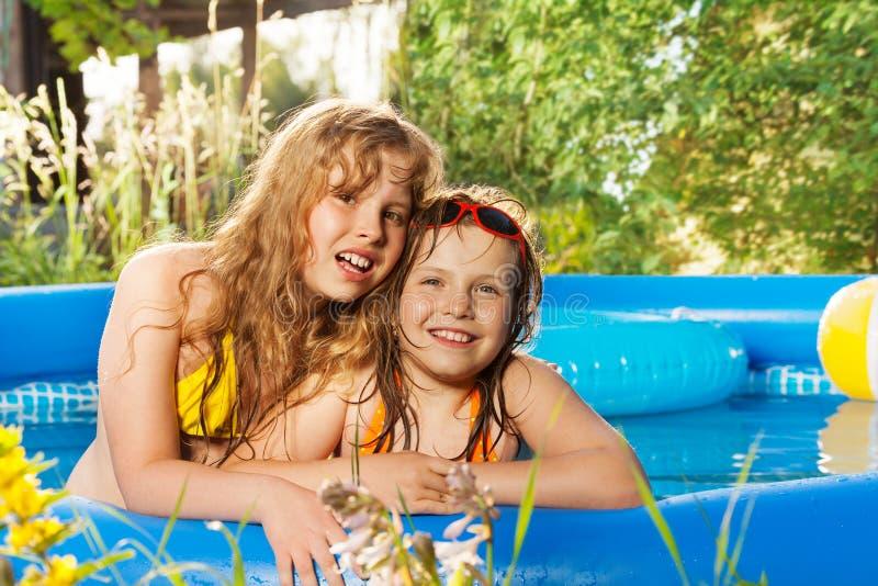 摆在可膨胀的水池的两个愉快的女孩 免版税库存图片