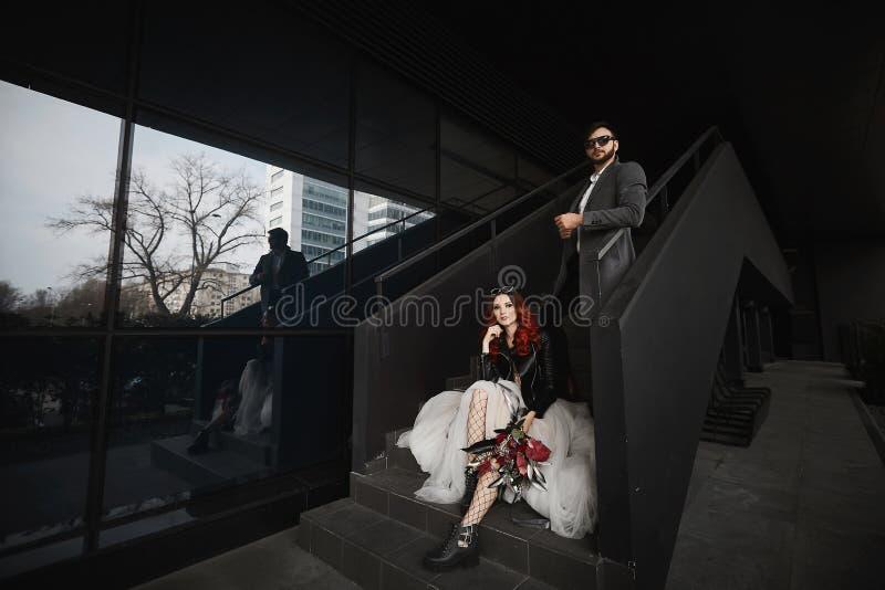 摆在台阶的凉快的夫妇在黑背景附近 免版税库存图片