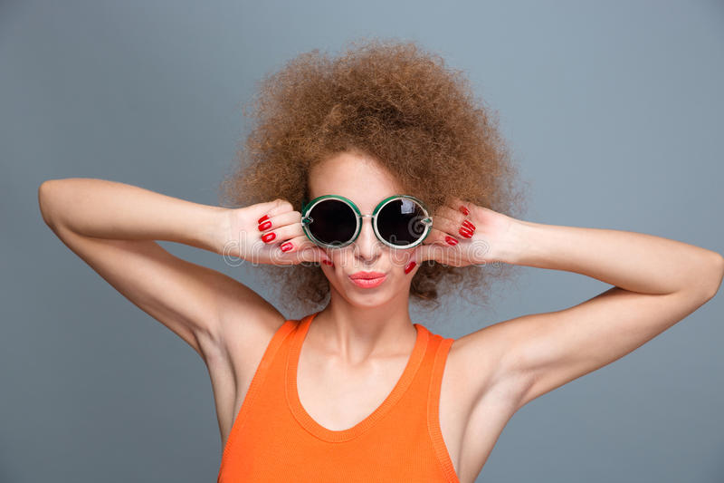 摆在和做鬼脸的凉快的确信的年轻女性 免版税库存照片
