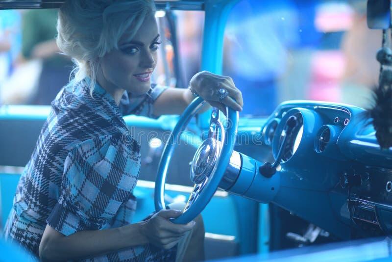 摆在和和在葡萄酒汽车附近的可爱的妇女 库存图片