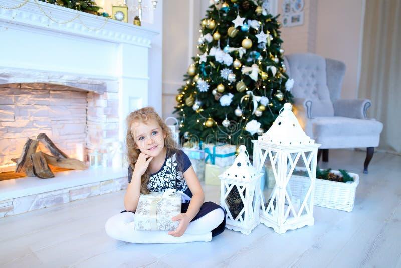 摆在和微笑对在白色新年的studi的照相机的逗人喜爱的女孩 库存图片