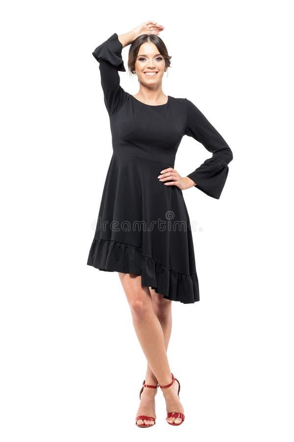 摆在和微笑对照相机的黑礼服的快乐的愉快的魅力妇女 免版税库存图片