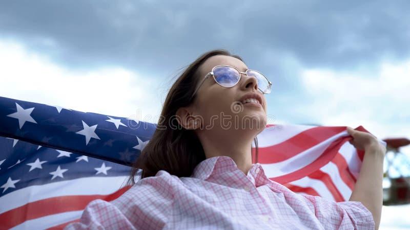 摆在和挥动美国旗子,美国独立日庆祝,爱国者的年轻女人 免版税图库摄影