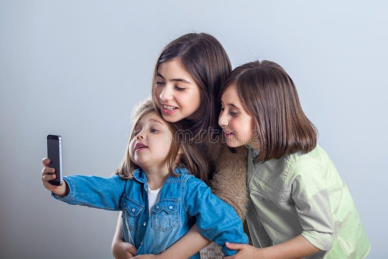 摆在和采取selfies的三个姐妹在演播室 免版税库存照片