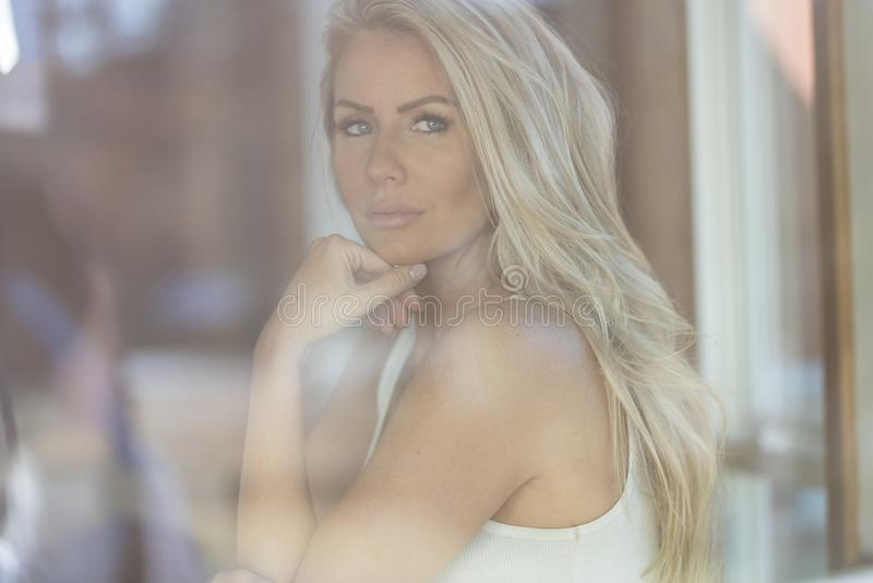 摆在咖啡馆附近的华美的白肤金发的模型 免版税库存照片