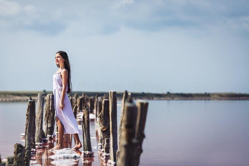 摆在咸桃红色湖的长的白色礼服的美丽的少女 免版税图库摄影