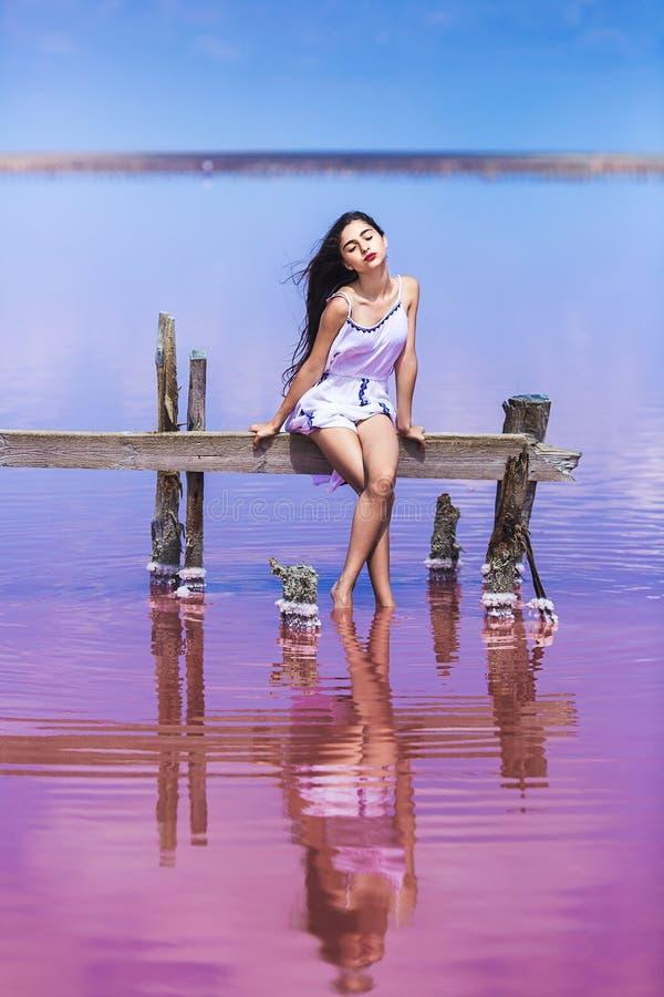 摆在咸桃红色湖的长的白色礼服的美丽的少女 免版税库存图片