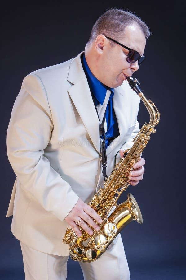 摆在唱歌的传神成熟使用的萨克斯管吹奏者画象  免版税库存图片