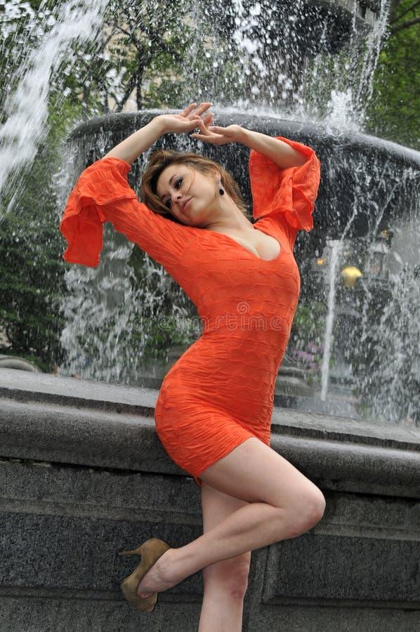 摆在喷泉前面的短的红色礼服的时装模特儿 免版税库存照片