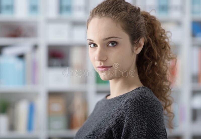 摆在图书馆的美丽的学生女孩 免版税图库摄影