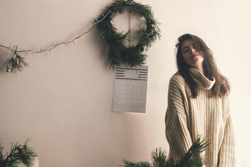 摆在土气屋子里的被编织的毛线衣的时髦的行家女孩  图库摄影