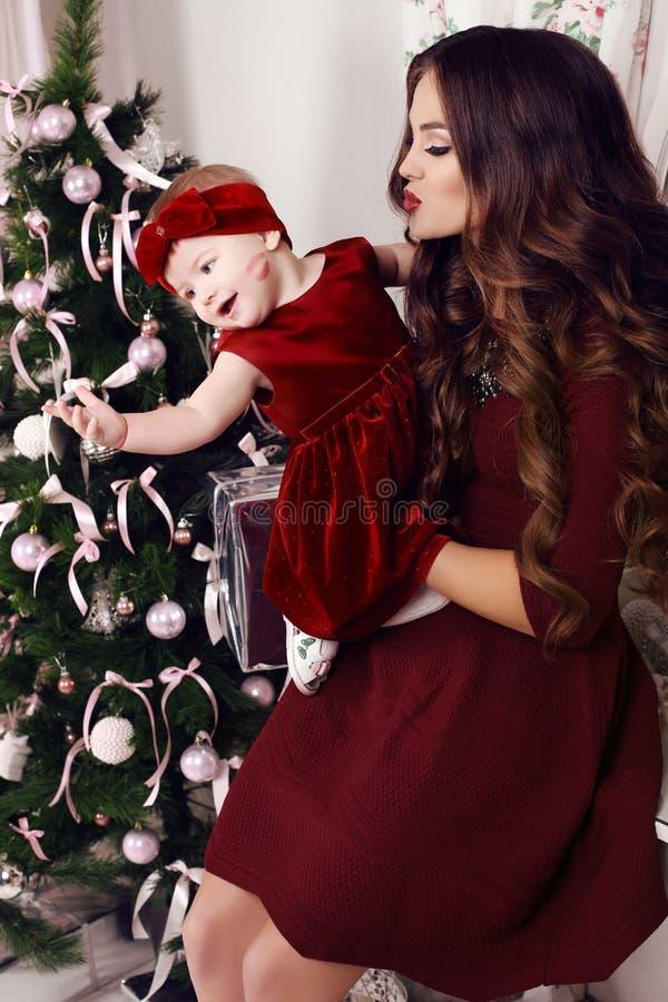 摆在圣诞树旁边的美丽的家庭假日照片 免版税库存照片