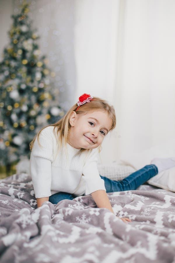 摆在圣诞树附近的一件白色毛线衣和蓝色牛仔裤的愉快的小女孩 免版税图库摄影