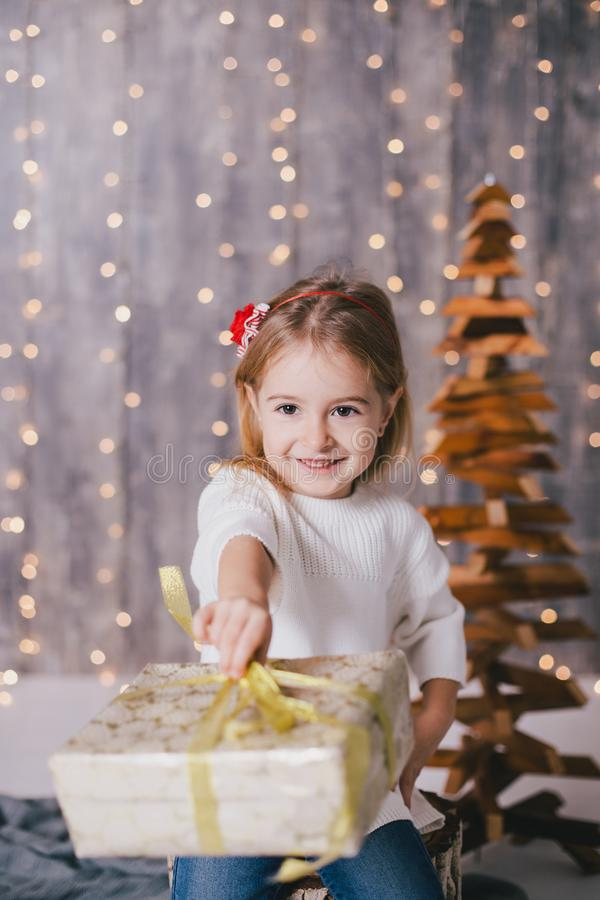 摆在圣诞树附近的一件白色毛线衣和蓝色牛仔裤的愉快的小女孩 免版税库存图片
